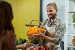Smiling vendor offering oranges to the woman at the counter Royalty Free Stock Images