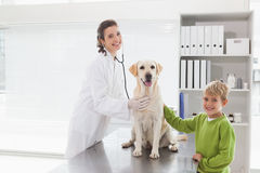 Smiling vet examining a dog with its owner Royalty Free Stock Images