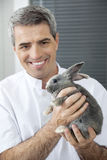 Smiling Vet Holding At Rabbit In Clinic. Smiling mature male vet holding at rabbit in clinic Stock Images