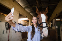 Smiling vet taking selfie with horse in stable. Smiling female vet taking selfie with horse in stable Stock Photography