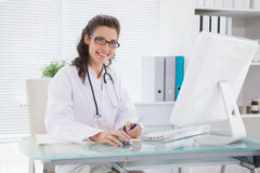 Smiling vet writing and using computer Stock Photos