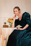 Smiling victorian woman sitting at table Stock Images
