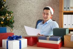 Businessman checking list of presents stock photography