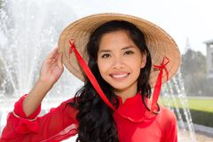 Smiling Vietnamese woman in a red Ao Dai. Vietnamese woman in a red Ao Dai and conical hat standing in front of a fountain smiling at the camera Stock Photo
