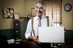Smiling vintage businessman holding a blank sign Royalty Free Stock Image