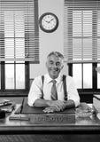 Smiling vintage director sitting at office desk Stock Photo
