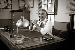 Smiling vintage director sitting at office desk Royalty Free Stock Photos