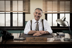 Smiling vintage director sitting at office desk Royalty Free Stock Photography