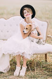 The smiling vintage-dressed bride with the black hat is hugging the lovely dog and sitting on the sofa in the sunny. Field Royalty Free Stock Photography
