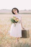 The smiling vintage dressed bride with the wedding bouquet and suitcase is posing to the camera. The sunny field Stock Image