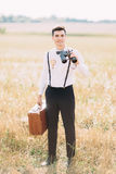 The smiling vintage dressed groom carrying the retro suitcase and binoculars is looking at the camera. The sunny field Stock Images