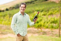 Smiling vintner holding bottle of wine Stock Image