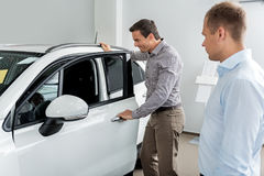 Smiling visitor watching at automobile design. Side view cheerful client looking at car interior while standing near it in dealership. Agent describing Royalty Free Stock Photography