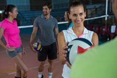Smiling volleyball player giving ball to teammate. Smiling female volleyball player giving ball to teammate at court Royalty Free Stock Photography