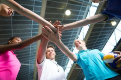 Smiling volleyball players and coach forming a hand stack Royalty Free Stock Photo