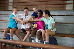 Smiling volleyball players and coach forming a hand stack Royalty Free Stock Photos