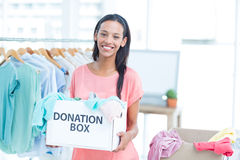 Smiling volonteer holding a box of donations Royalty Free Stock Photo