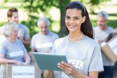Smiling volunteer brunette using tablet pc Stock Images