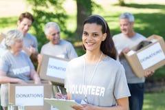 Smiling volunteer brunette writing on cipboard Royalty Free Stock Images