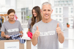 Smiling volunteer doing thumbs up Royalty Free Stock Image