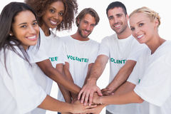 Smiling volunteer group putting hands together stock photos
