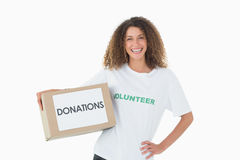 Smiling volunteer holding a box of donations with hand on hip Stock Photography