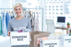 Smiling volunteer holding a box of donations Stock Images