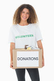 Smiling volunteer holding a box of donations Stock Photography