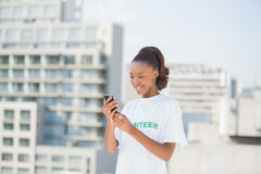 Smiling volunteer holding her mobile phone Royalty Free Stock Photo