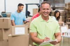 Smiling volunteer man taking notes holding clipboard