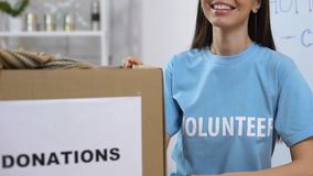 Smiling volunteer standing near boxes with donated clothing, homeless assistance. Stock footage stock video