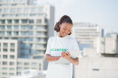 Smiling volunteer woman taking notes holding clipboard Stock Photo