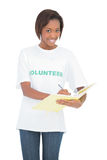 Smiling volunteer woman writing on notebook Stock Photos