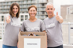 Smiling volunteers with donation box doing thumbs up Royalty Free Stock Photos