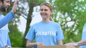 Smiling volunteers giving high five near donation boxes outdoor, charity project. Stock footage stock video