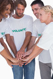 Smiling volunteers putting hands together Royalty Free Stock Photos
