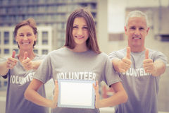 Smiling volunteers showing blank tablet Stock Photography