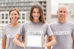Smiling volunteers showing blank tablet Stock Image