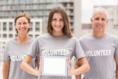 Smiling volunteers showing blank tablet Stock Image