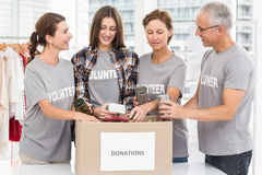 Smiling volunteers sorting donation box Royalty Free Stock Photos