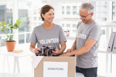 Smiling volunteers sorting donation box Royalty Free Stock Image