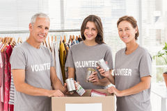 Smiling volunteers sorting donations. Portrait of smiling volunteers sorting donations in the office Royalty Free Stock Images