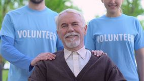 Smiling volunteers standing behind old disabled person, social support, charity