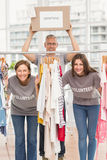 Smiling volunteers standing between hanged clothes Stock Photography