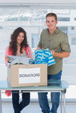 Smiling volunteers taking out clothes from a donation box Stock Images