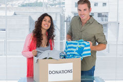 Smiling volunteers taking out clothes from donations box Stock Photo