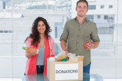 Smiling volunteers taking out food from donations box Stock Photo