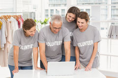 Smiling volunteers using laptop together Royalty Free Stock Photography