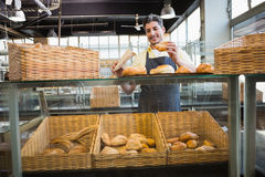 Smiling waiter in apron choosing bread. At the bakery Stock Photography