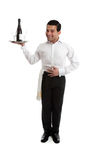 Smiling waiter or bartender. Smiling waiter, butler, bartender ot other attendant holding a silver tray with a bottle or wine and glasses. White background stock images